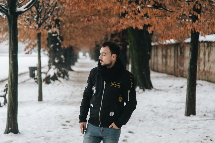 Man in warm clothing standing on snow against trees