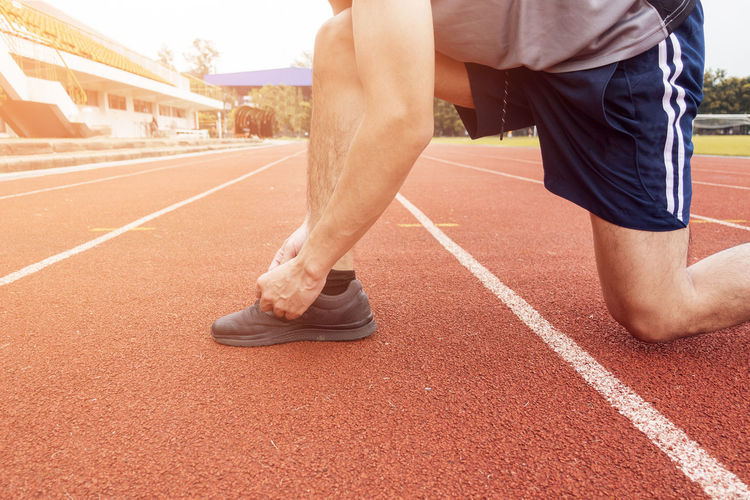 Low section of man tying shoelace on running track