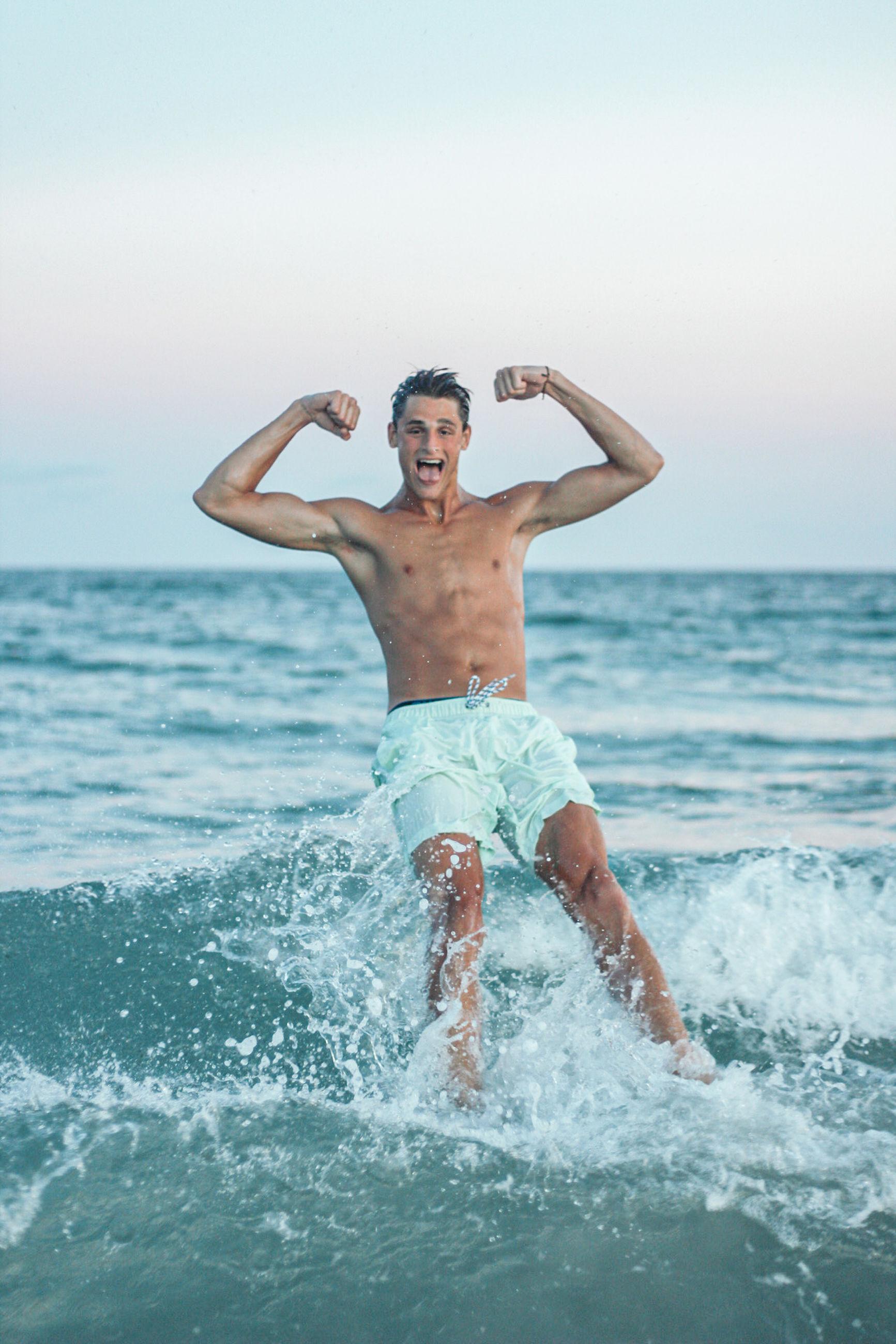 FULL LENGTH OF SHIRTLESS MAN SPLASHING WATER IN SEA