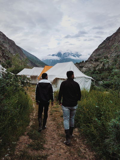 2 brothers walking down a valley camp site in ladakh overlooking majestic mountains and river