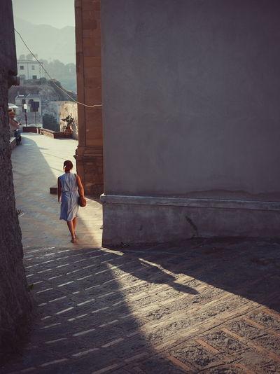 Rear view of woman walking on footpath in town