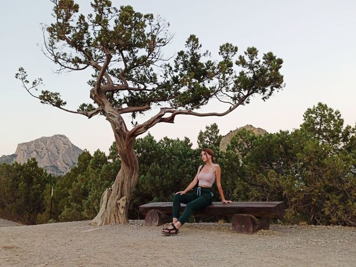 Young woman sitting on bench against trees