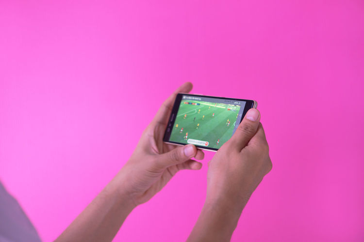 Close-up of hand holding mobile phone over pink background