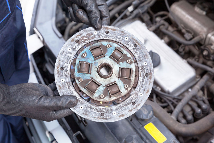 Auto mechanic wearing protective work gloves holding old clutch plate disc over a car engine Repairing Mode Of Transportation Mechanic Machine Part Auto Repair Shop Car Clutch Clutch Plate Auto Mechanic Car Service Spare Parts Spare Parts Repair Replace Automotive Coupling Engine Friction Gear Transmission Vehicle Holding