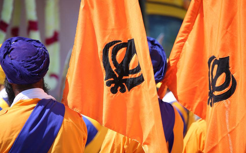 symbol of the Sikh religion called KHANDA formed by two scimitars on the orange flags and the man with the blue turban Event Flame Orange Sikhi Clothing Demonstration Flag Khanda Manifestation Nagar Nagar Kirtan Outdoors Parade People Religion Religious  Sikh Sikh People Sikhism Sikhlife Sikhs Symbol Turban