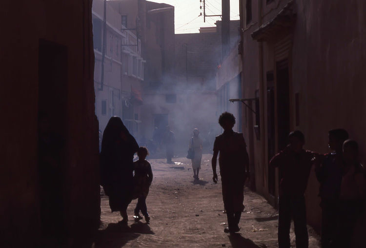 Residents in the walled area in Marrrakech, Morocco called the Medina. Africa Arabic Architecture Building Built Structure Children Fine Art Photography Islam Islamic Mammal Marakesh Marrekech Medina Morocco Muslim Outdoors People Silhouettes Smoke Walls Women