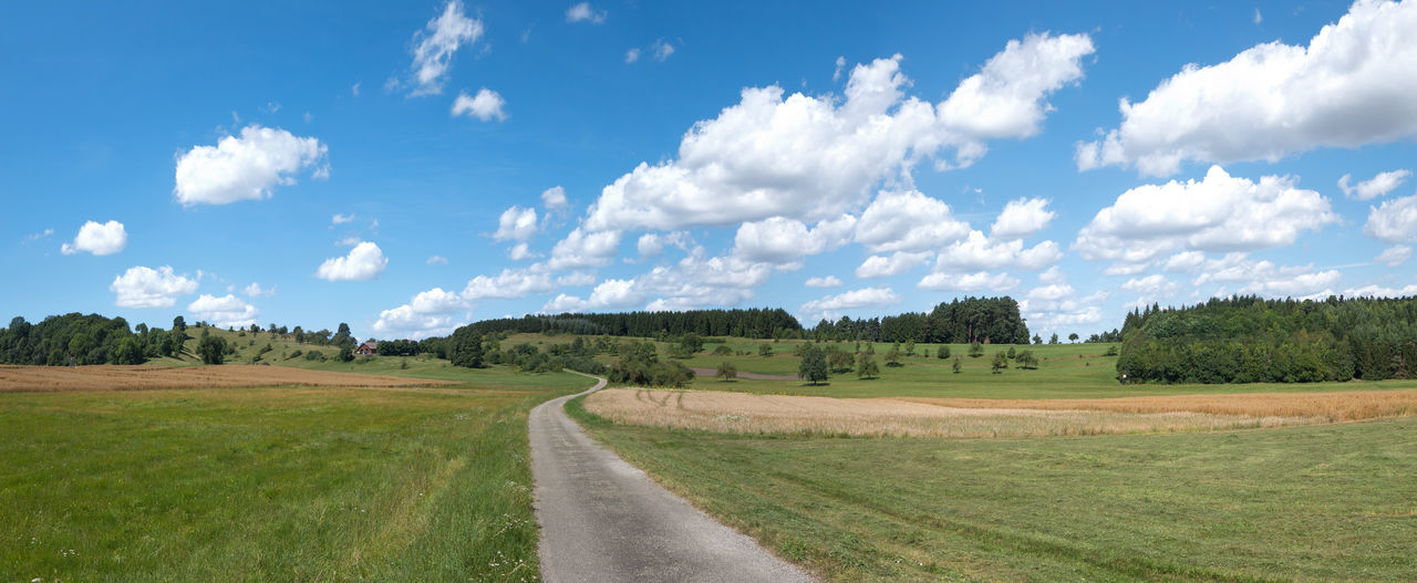 Way through meadows and fields in a rural landscape in summer with blue and white sky Cloud Cloudscape Field Footpath Grass Land Nature Panorama Panoramic Path Rural Scenic Tree Countrside Forest Hilly Idyllic Landscape Meadow Outdoor Scenery Season  Sky Summer Way