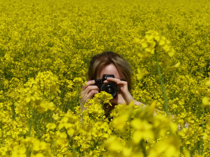 Portrait of young woman photographing with yellow flowers