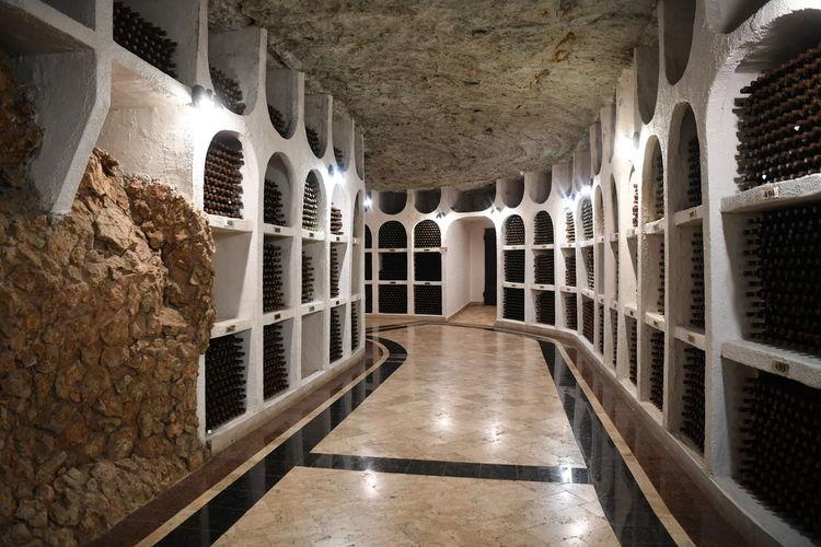 Bottles in shelves of illuminated corridor