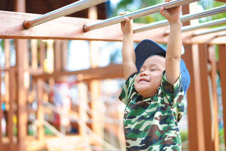 Cute boy hanging from monkey bar at playground