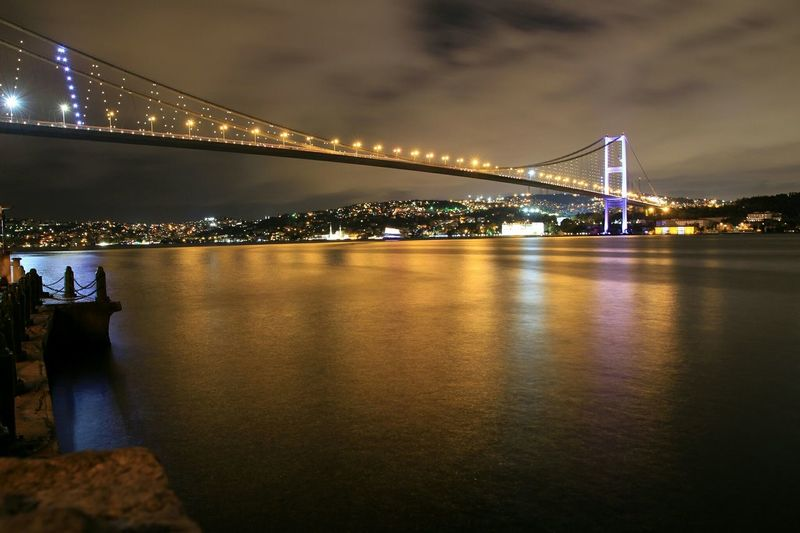 Low angle view of bosphorus bridge over river against cloudy sky at dusk