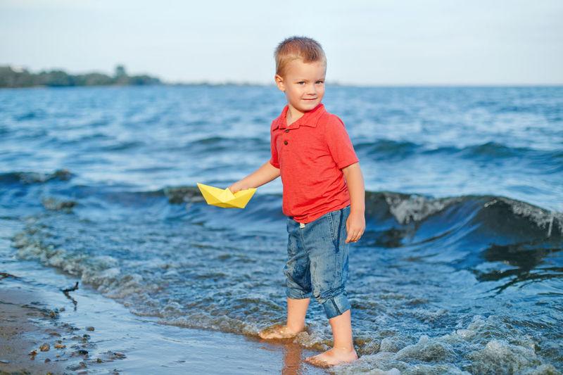 Full length of cute boy in sea