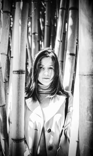 Portrait of young woman standing amidst bamboo grooves
