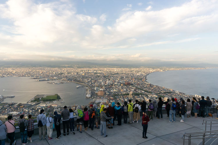 High angle view of people standing at mount hakodate in city against cloudy sky