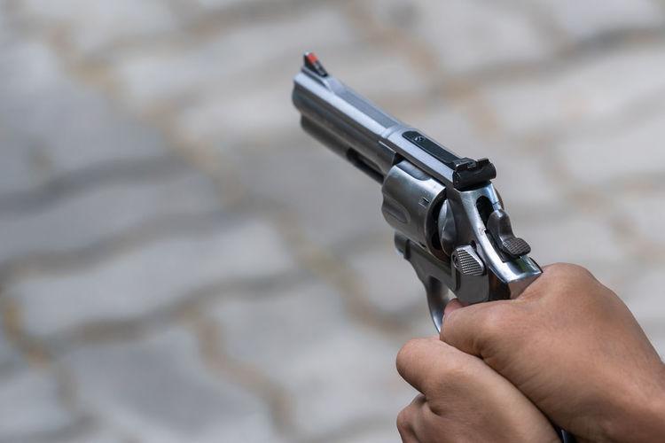 Close-up of hands holding gun