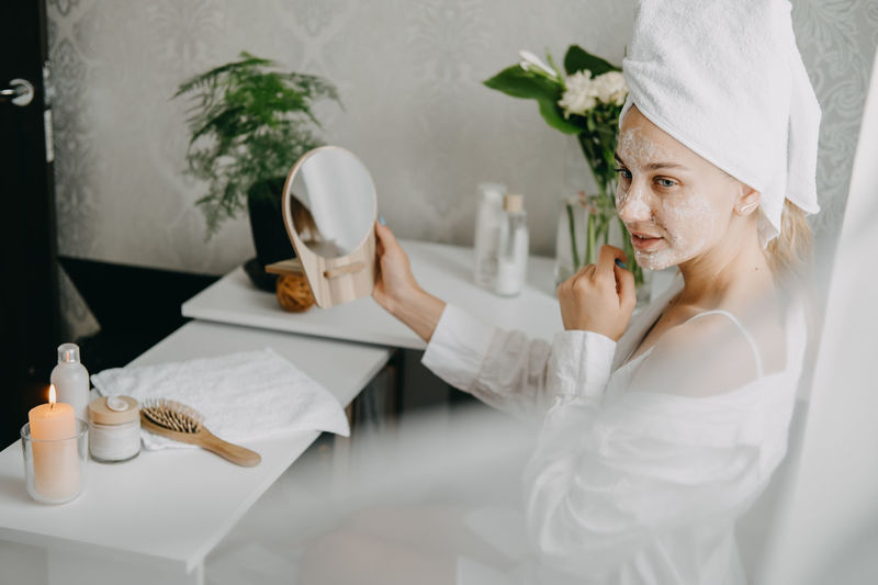 Young woman in white towel chilling in bedroom and making clay facial mask near mirror.