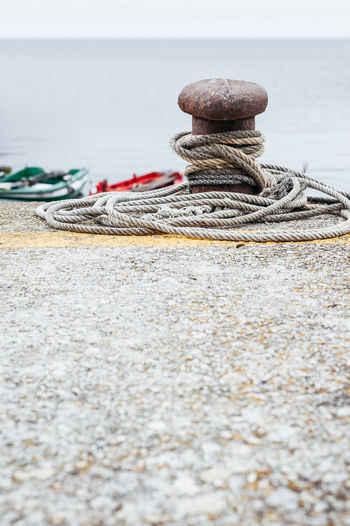 Harbor Rope Bollard Close-up Day Land Moorage Nature Nautical Vessel No People Outdoors Pebble Port Rope Sea Selective Focus Sky Solid Stack Still Life Strength Surface Level Tied Up Transportation Water