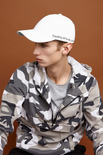 Portrait of young man wearing hat against gray background