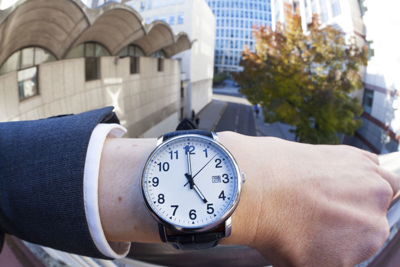 Cropped Hand Of Businessman Wearing Wristwatch By Railing In City