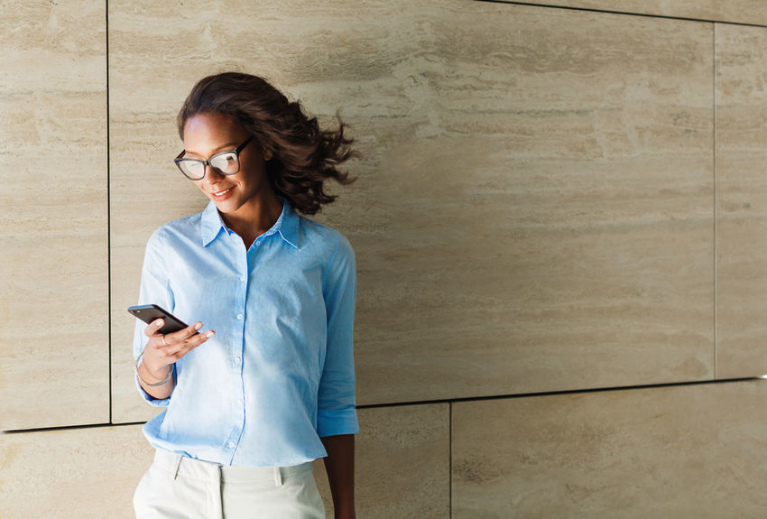 Business Person Technology One Person Young Adult Holding Cell Phone  Communication Woman Entrepreneur Professional Copy Space Eyeglasses  Outdoors Standing Texting African American Modern