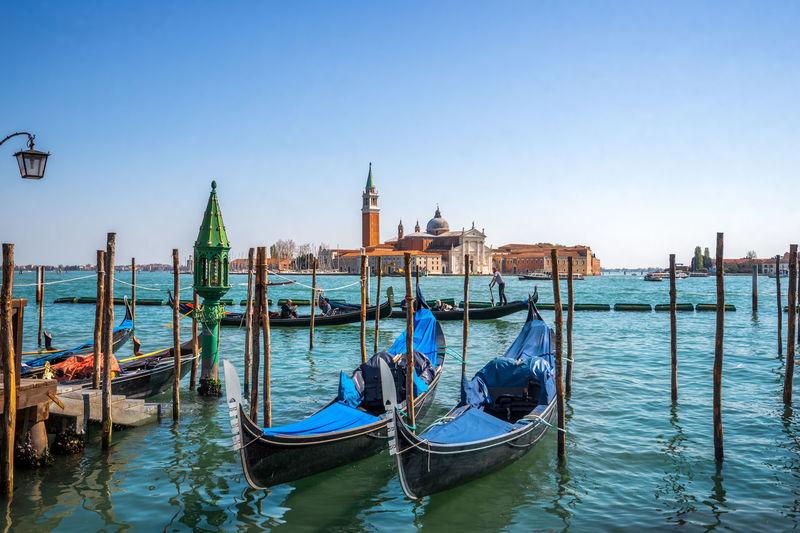 Gondolas moored on grand canal against san giorgio maggiore church