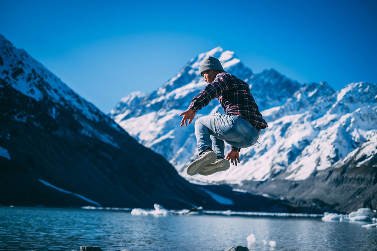 Man jumping in mid-air by snowcapped mountains against sky