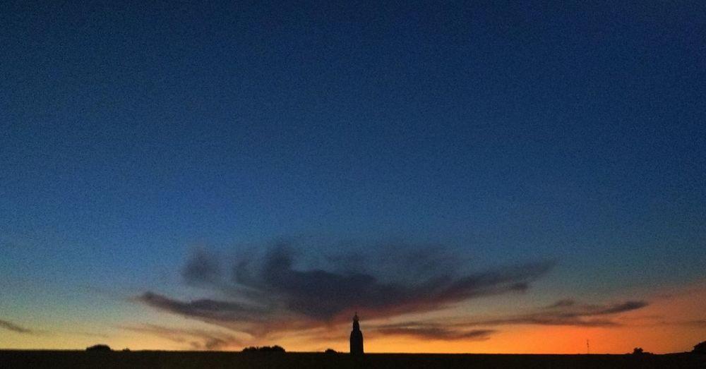 Silhouette landscape against blue sky during sunset