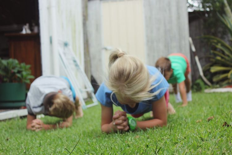 Children having a Planking Competition Grass Lawn Backyard Childhood Child Kids Family Girl Kid Boy Siblings Rivalry Sibling Fit Fitness Sport The Portraitist - 2016 EyeEm Awards The Essence Of Summer Girl Power Natural Light Portrait