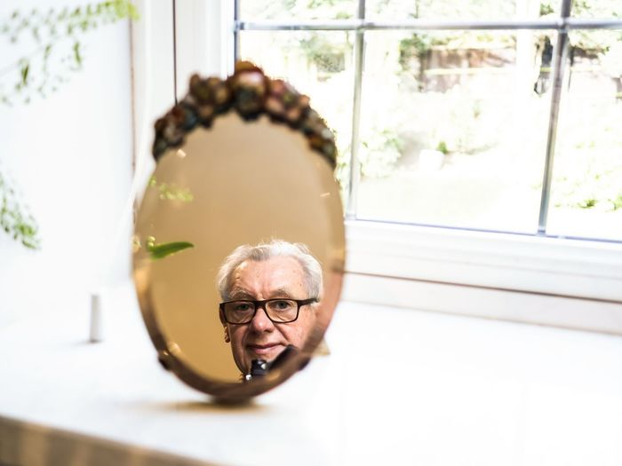 Portrait of man wearing eyeglasses at home