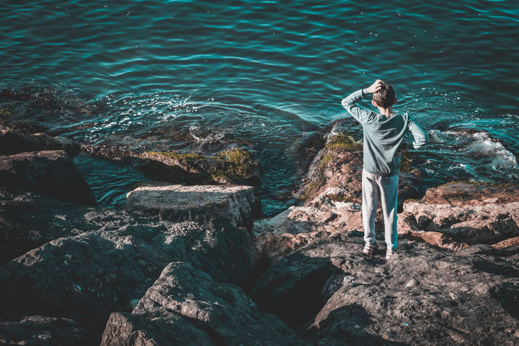 Young man standing on rock by sea