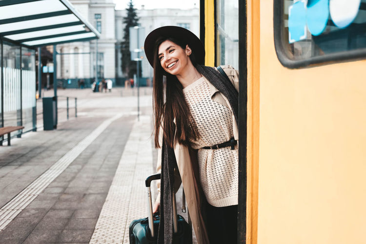 Portrait of smiling woman in train at railroad station