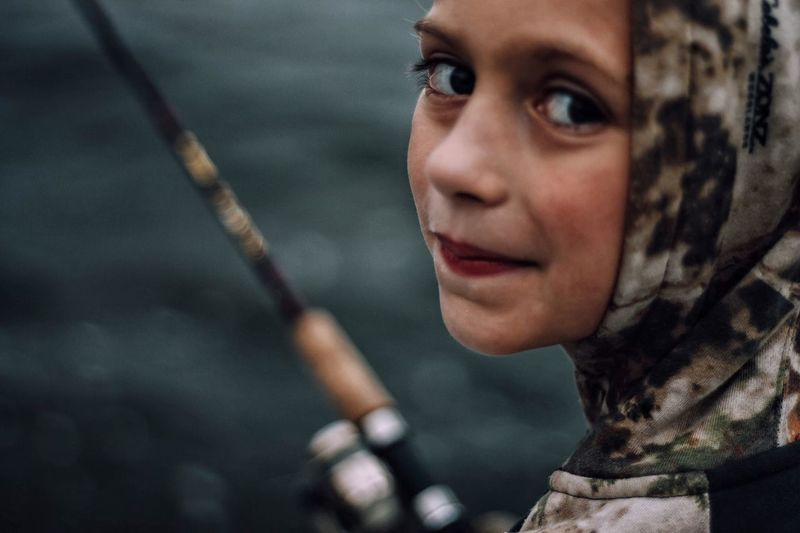Close-up portrait of girl fishing in lake