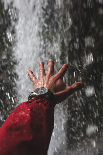 Cropped hand of person gesturing against waterfall