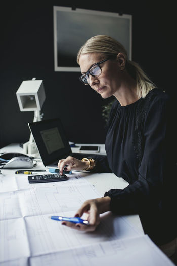 Businesswoman looking at blueprint while using calculator on desk