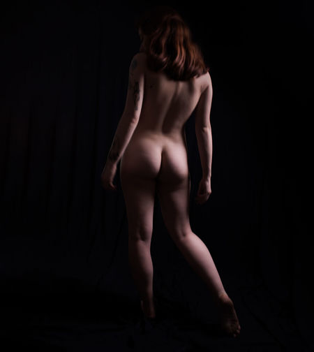 Rear view of shirtless woman standing against black background