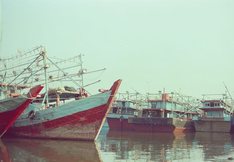Fishing boats moored at harbor against clear sky
