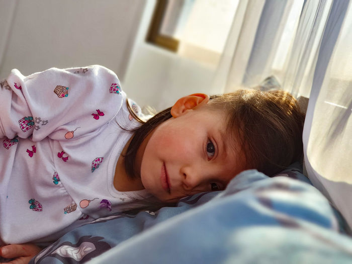 Portrait of cute girl lying on bed at home
