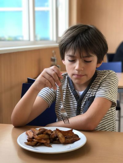 Boy having potato chips while sitting on chair at restaurant