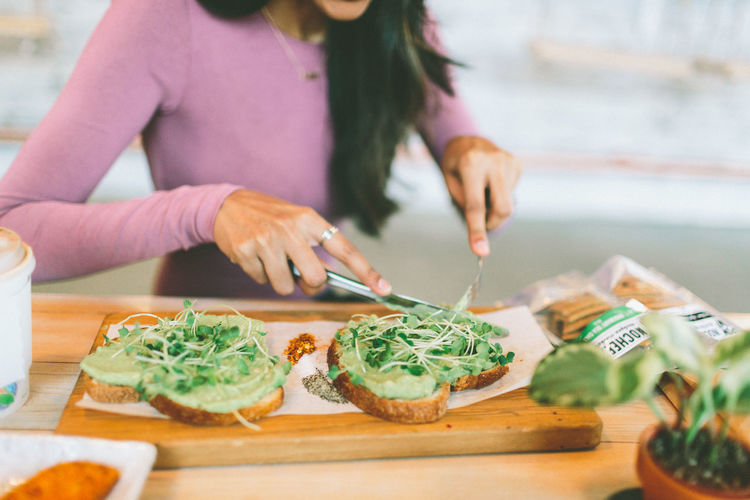 A woman cutting a piece of avocado toast in a cafe. Food And Drink Food Table Women Healthy Eating Freshness Indoors  Vegetable Adult Avocado Toast Cutting Eating Lunch Breakfast