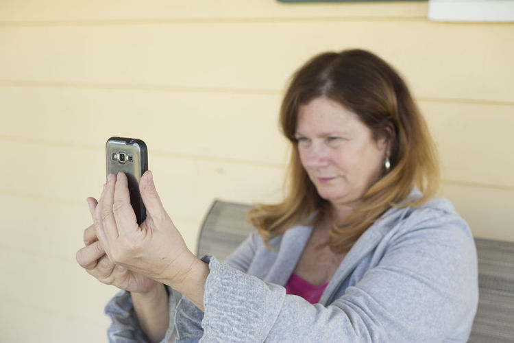 Woman Taking Selfie Through Mobile Phone While Sitting On Chair At Porch