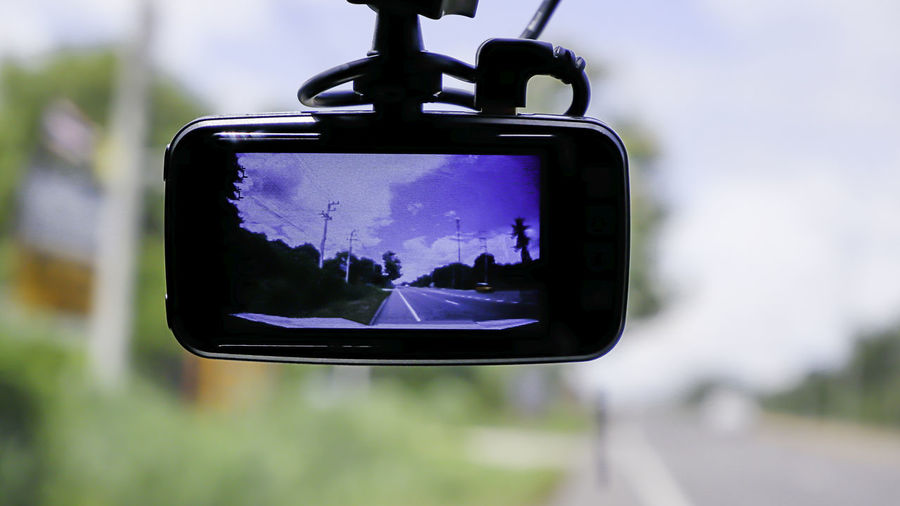 Close-up of smart phone on side-view mirror