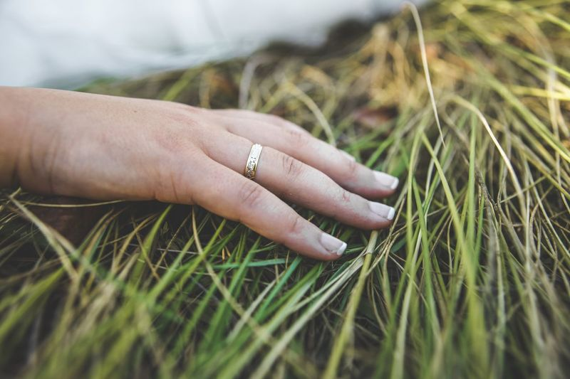 Close-up of ring on woman hand over grass
