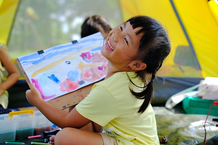 Girl painting on paper while sitting against tent