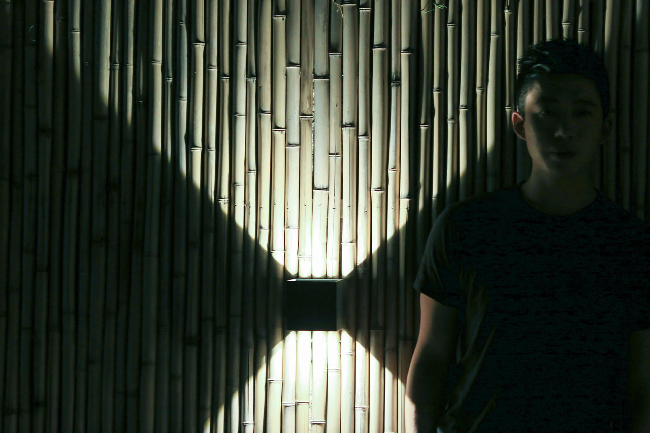 Young Man Standing Against Wooden Wall At Night