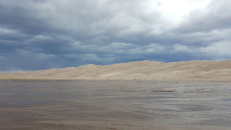 Scenic view of sand dunes against cloudy sky
