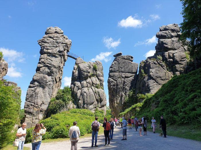 Rear view of people walking on rocks against sky
