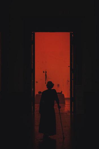 Rear view of silhouette man standing against door in building