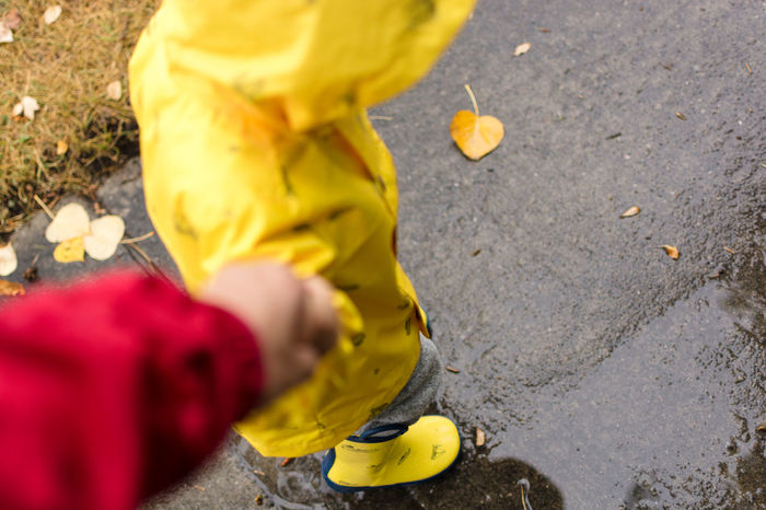 Little boy wearing a yellow raincoat holding hands with his dad on a rainy day. Autumn Holding Hands Rainboots Childhood Close-up Day Fall Kid Outdoors Parent People Raincoat Rainy Real People Rubber Boots Toddler  Walking Wet Yellow Paint The Town Yellow