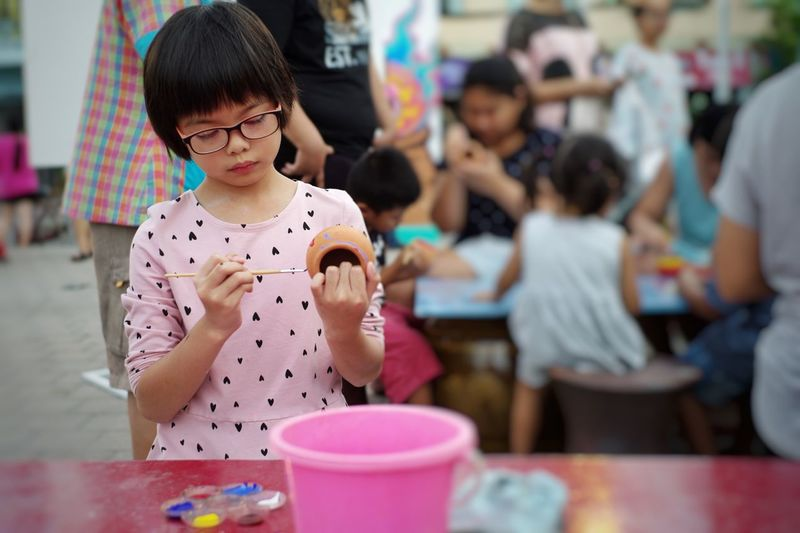 Portrait of asian little girl painting on a small clay pot Color Workshop Creative Painting Drawing Child Real People Childhood Women Glasses Focus On Foreground Incidental People Girls Eyeglasses  Table Hairstyle