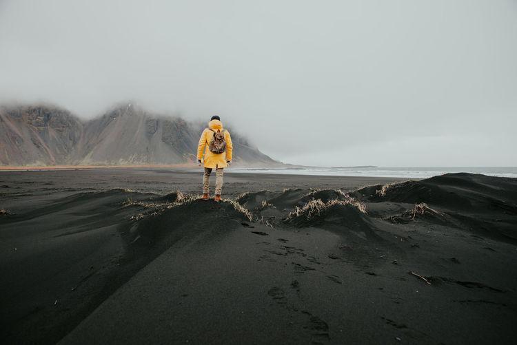 Man on black sand in desert